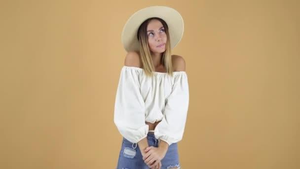 atraktivní Mladá blondýnka nosí bílé košile a slaměný klobouk, představuje na pozadí,