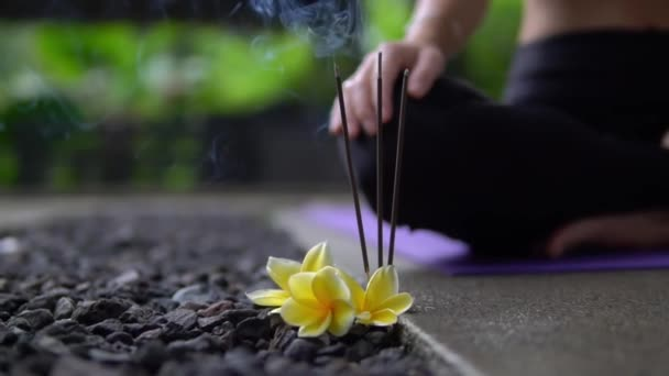 close up of burning incense sticks with yellow flowers on stone floor outside