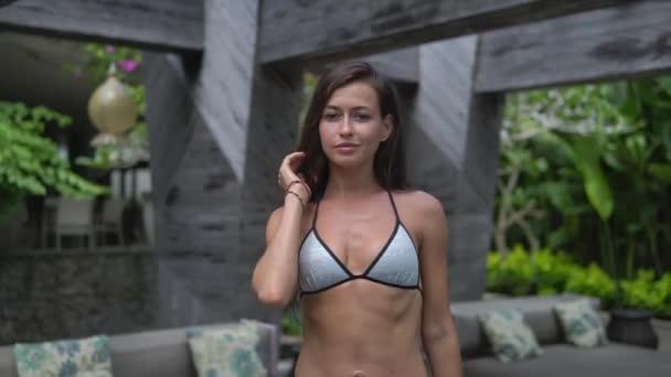 Slender adult girl in bathing suit going towards camera, model walks outside