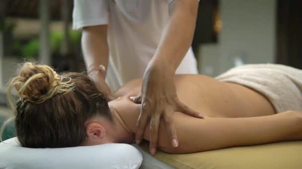 dívka ležící obličejem dolů, má v přírodě na krku masáž, tropické lázně, rekreace
