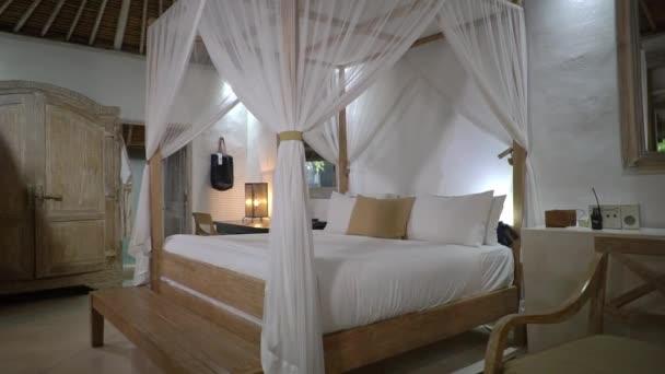 Stylová světlá ložnice v hotelu s lehkým barevným nábytkem, bílá čtyřplakátová