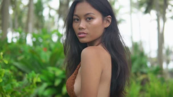 close up, slow motion shooting of young asian model in beauteous pose outdoors,