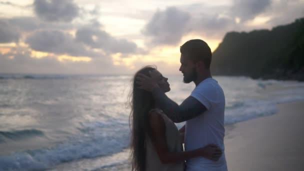 szerelmesek csókolózás naplementekor a tengerparton, romantikus este egy egzotikus helyen
