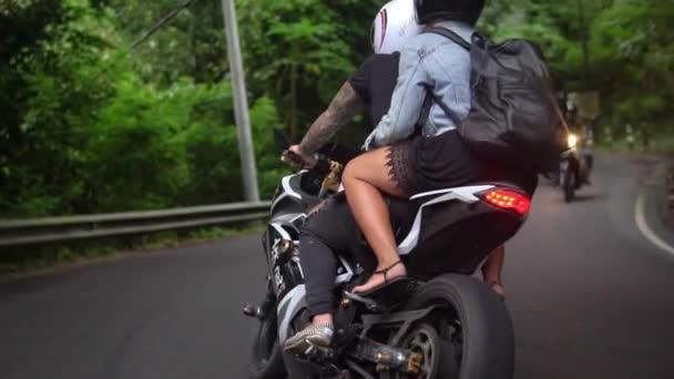 lidé na motorce jezdit na venkovské silnici v tropech, mladí manželé mají cestu