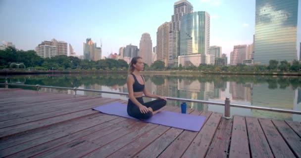 Mladá žena si dává pauzu po náročném pracovním dni, užívá si přírody v městském parku u jezera.
