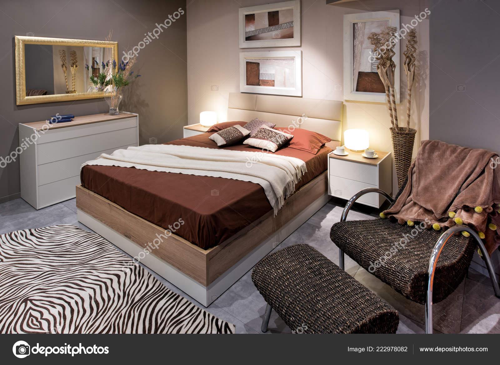 dubbele slaapkamer design concept met bruin persoonshoogslaper en comfortabele fauteuil met ottomaanse zebra tapijt op de vloer en schilderijen aan de muur