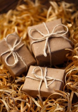 Rustic little gift boxes lie in natural wood shavings. Concepts - holiday gift, eco-friendly packaging, rural-style gift wrapping.