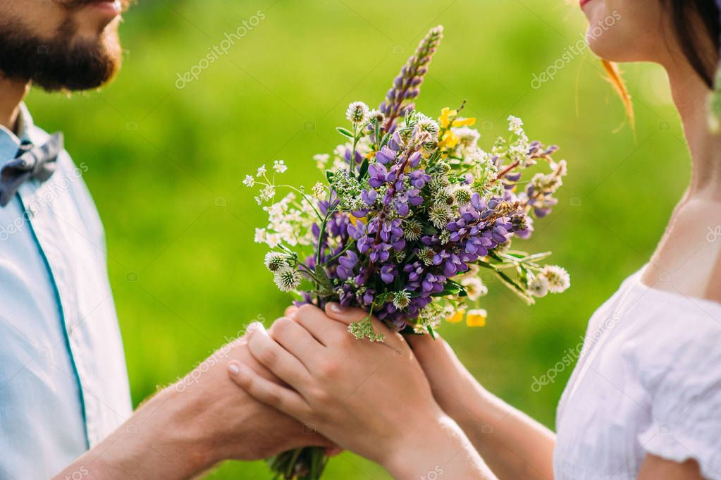 Romantic guy gives a girl a rustic bouquet of wild flowers