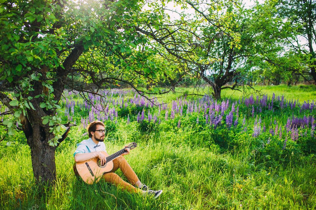 Romantic concept. Young man playing guitar outdoor under the tree on a lupine background.