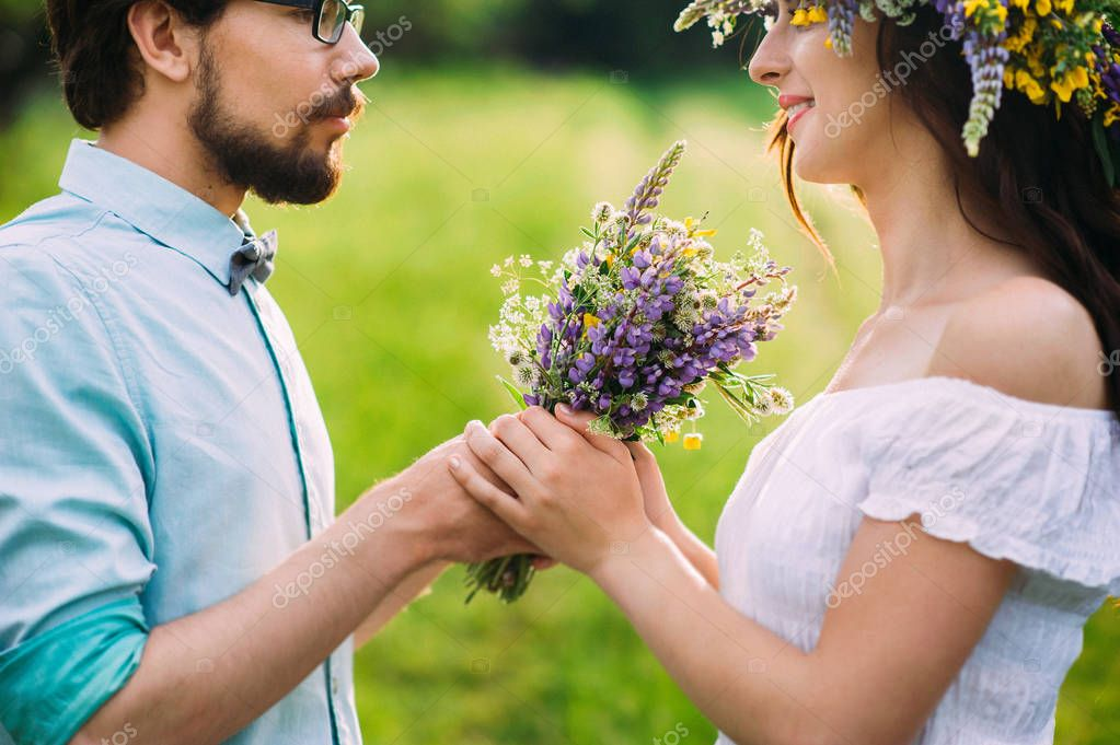 handsome guy with a beard in a blue denim shirt gives field flowers girl