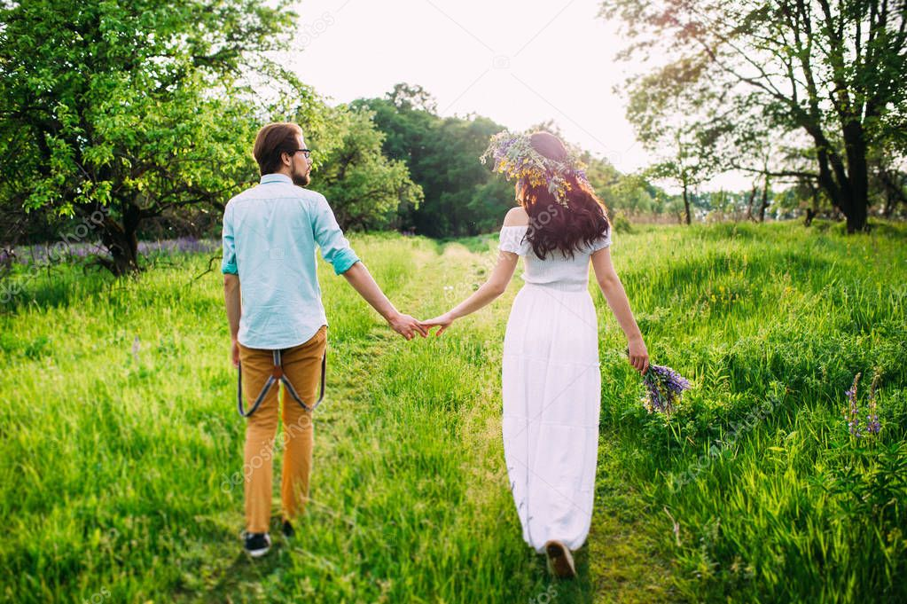 romantic concept. Young couple holding hands walking through a meadow.