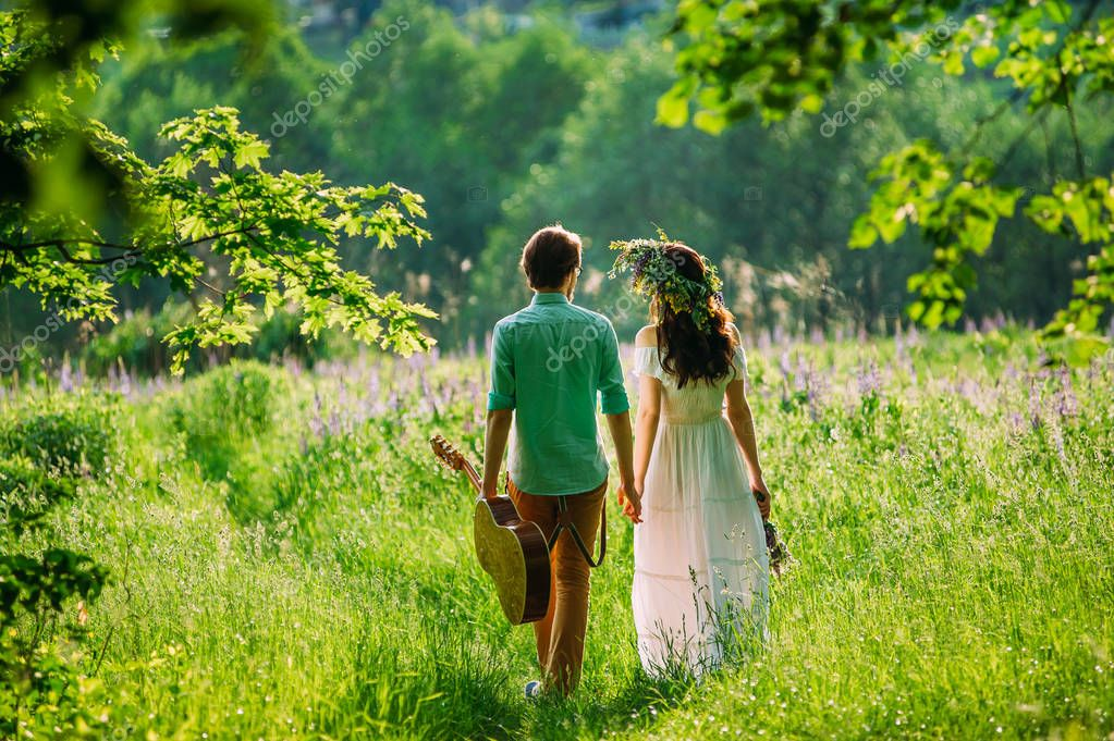 a boy and a girl in love walking in deep grass