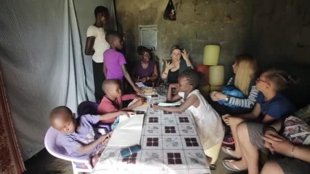 Kisumu, Keňa - 23. května 2018: Velká skupina lidí, kteří sedí v útulku africké rodiny. Kavkazské muži a ženy mluví