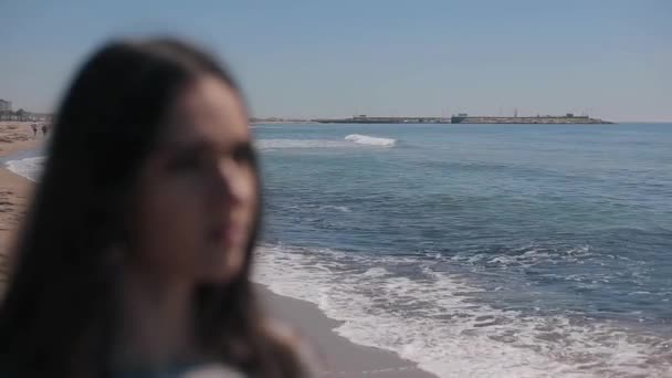 A defocused close view of a girl against a beautiful background of the sea and the beach. The girl puts on shades and the view becomes focused