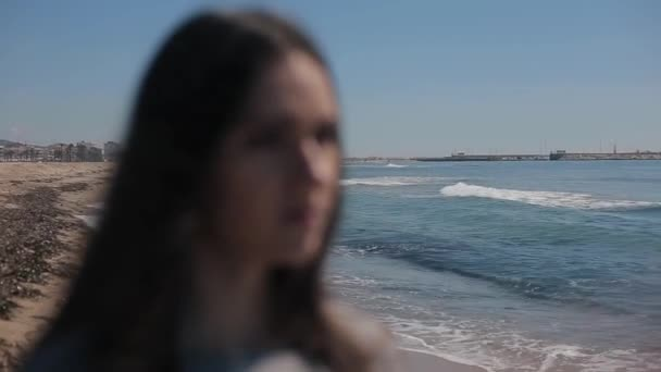 A close-up of a girl on the seashore on a beautiful sunny day. The focus on the background. The girl putting on sunglasses. The sea reflection in the shades. Focus shifting to the girl. Blurred