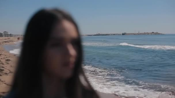 A blurred portrait of a girl against scenic view of beach and sea on clear sunny day. The girl puts on sunglasses. Focus shifts from the background to the girl. Sea waves reflection in the shades