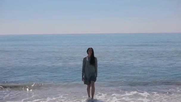 A beautiful girl in a short dress walking out of the sea and going towards the camera