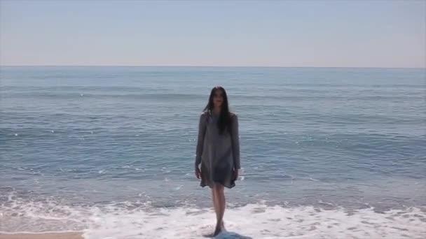 Krásná sexy holka vyleze z moře, se zastaví a přijímá sama s jednou rukou. Zpomalený pohyb