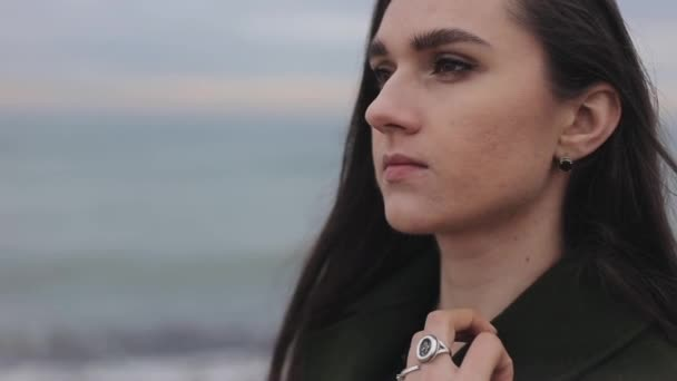 A beautiful sexy girl touching her long loose dark hair while standing against sea background on a cold day. A close view