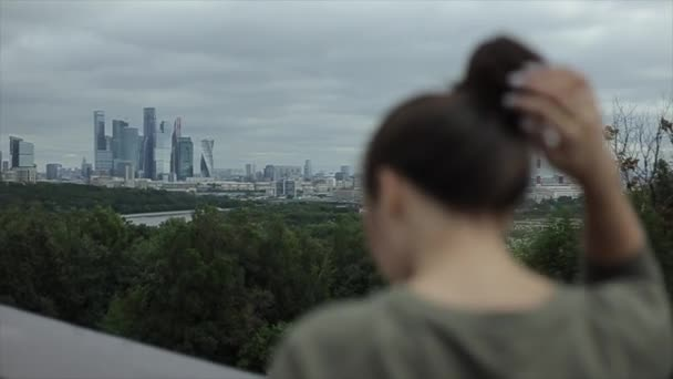 Cityscape. A pretty girl with long hair watches the landscape view, lets her hair down, and turns around