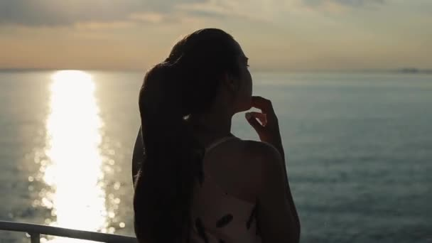 A beautiful girl enjoying the view of the river at sunset. Rear close-up half-body view. Travelling on a cruise ship along the river