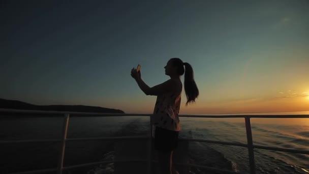 Krásná dívka s dlouhými vlasy vyfotografuje sama na svém smartphonu před řeky, kopce a obloha za soumraku