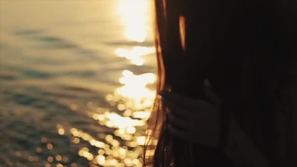 Lányok hosszú, barna haj, és a naplementét tükörképe a vízben