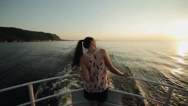 Rear view of a beautiful girl standing on a bow of the ship looking at the beautiful landscape of mountains, river, sky, and sunset