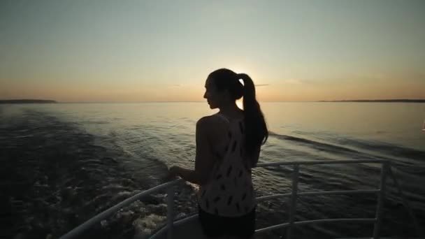 Side view of a beautiful girl posing on boats bow in sunset time