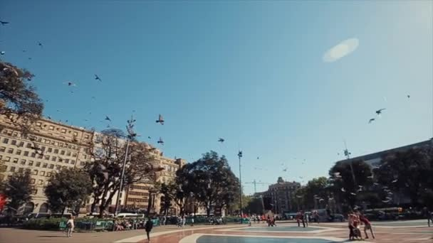 Barcelona, Spain - April 27, 2018: A lot of pigeons are flying in the air over the crowded square in Barcelona, Spain