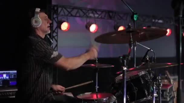 Bobruisk, Fehéroroszország - július 31, 2018: Rock koncert. Egy érett férfi Dobos dinamikusan dobolni egy koncerten. Koncert világítás