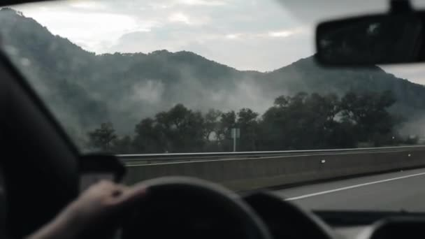 Driving high in the mountains in foggy weather. View from inside the car