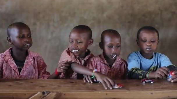 Keňa, Kisumu - 20 května 2017: Plešatý krásné africké kluky sedí u stolu a hraní s hračkami, auta