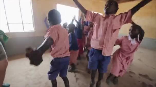 kenya, kisumu - 20. Mai 2017: fröhliche afrikanische Kinder wiederholen Tanzbewegungen nach kaukasischen Männern.