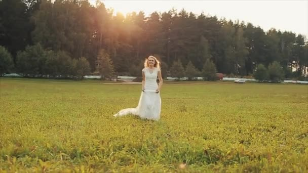 A beautiful bride runs towards the camera in the field. Amazing landscape in the background. Slow motion