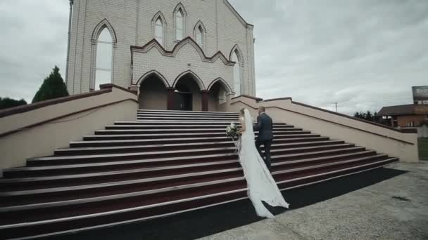 Back view of a bride in a long white dress and a groom going upstairs of a beautiful building