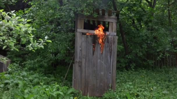 Mladý muž z hořící vesnice WC a snaží uhasit oheň hasicí přístroj. Hořící dřevěný dům. Budova v plamenech