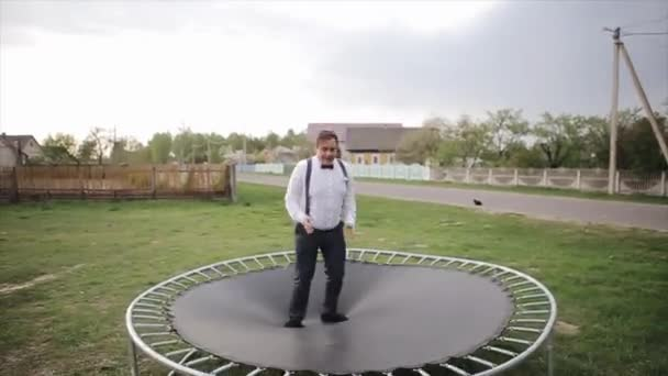 695672f40 A young man in black trousers with braces and a white shirt with a bowtie  jumps on a trampoline– stock footage