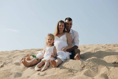 Happy family with daughter in white clothes are sitting toghether in desert sand dune.