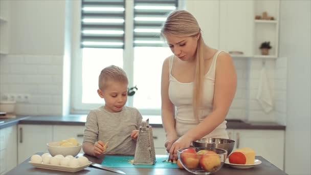 Mladá krásná kavkazské matka s bílými vlasy a syn vařit ve světlé kuchyni. Máma učí syna vařit.
