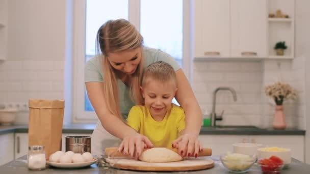 Krásná blond chlapec pomáhá matka vařit. Máma a syn v barevné košile roll z těsta. Maminka stojí za.