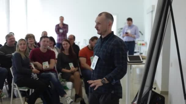 Misk, Belarus - July 23, 2018: Caucasian peaker in a plaid shirt is speaking on the stage over the presentation screen in the education seminar