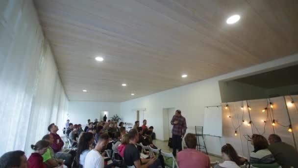 Misk, Bělorusko - 23 července 2018: Kavkazský peaker v kostkované košili mluví na jevišti během prezentace obrazovka v Pedagogický seminář. Kamera se pohybuje doplň.