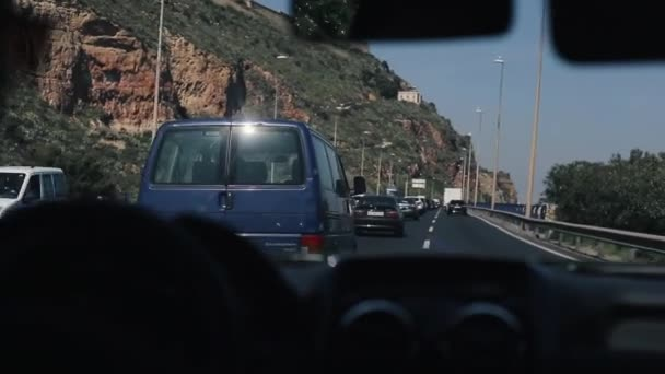 Inside view of the car. Driving car on the mountain road. Car rides on serpentine. POV view. Couple sitting in the front seats. Big brown mountain nearby
