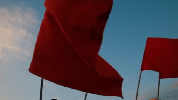 Crowd waving red flags against blue sky.