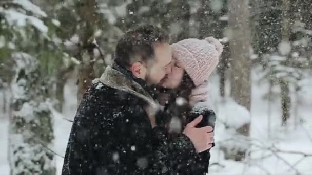 Young beautiful caucasian couple kissing under a snow in a winter forest. Fashionable millennials having fun toghether. Candid footage of young couple in forest. Slow motion.