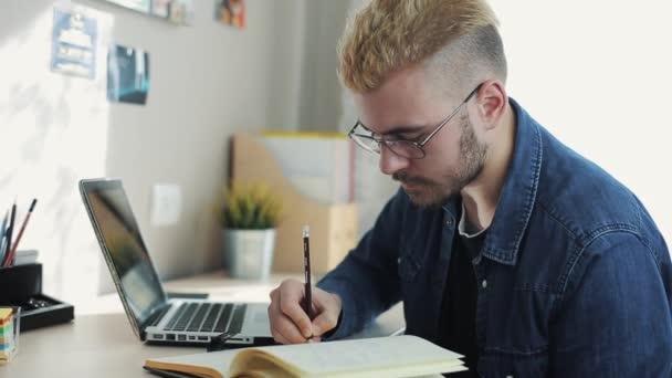 Detailní záběr portrét mladé atraktivní muž s brýlemi a žluté vlasy dělá poznámky na deník. Doma na volné noze pracovní na stole. Pomocí poznámkového bloku. Stylový úspěšný muž pracující na stůl