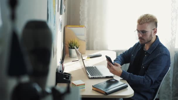 Young attractive businessman wearing glasses with yellow hair working at home. Using mobilephone sitting at the desk with laptop. Stylish Successful man working at desk
