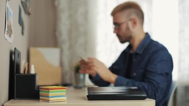 Fiatal férfi diák és stílusos fodrász szemüveg teszi jegyzetek matrica laptop és a napló az íróasztal asztalon. Oktatás, és az emberek koncepció.