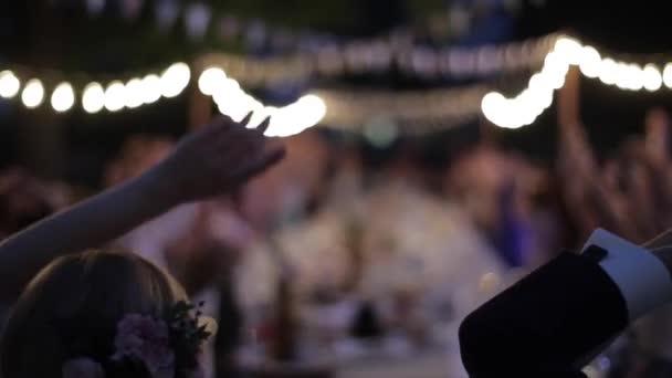Fehéroroszország, Minsk - 2018. május 30.: Szabadtéri esküvő ünnep retro garland. Az emberek az asztalnál. Esküvői bankett. Éjszakai. Esküvői beállítása. Menyasszony és a vőlegény, miután funwith a vendégek. Emberek integetett a